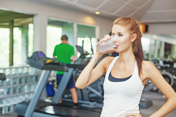 woman in gym having a glass of water