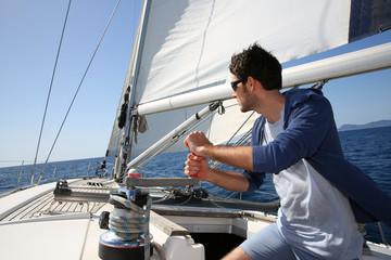 Mężczyzna żegluje z żaglami out w słonecznym dniu
