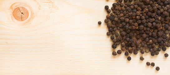 black pepper on wooden background - top view