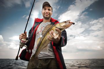 Happy angler with zander fishing trophy