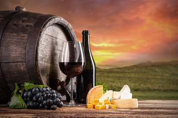 Red wine still life with vineyard on background