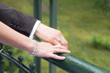 Bride and groom holding hands on the bridge