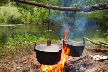 gotowanie posiłku na ognisku w metalowych naczyniach