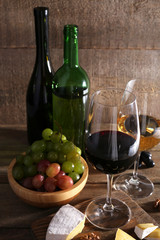 beautiful still life with wine, cheese and ripe grape