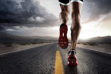 Tło sportowe. Biegacz cieki biega na drogowym zbliżeniu na bucie.