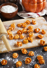 Uncooked tortellini with cheese on a table