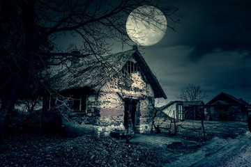Spooky scene of haunted house and moon