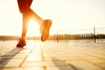Runner feet running on road closeup on shoe. woman fitness sunri