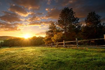 Malowniczy krajobraz, ogrodzone ranczo o wschodzie słońca