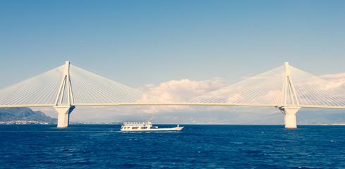 Ferry boat sailing under suspension bridge
