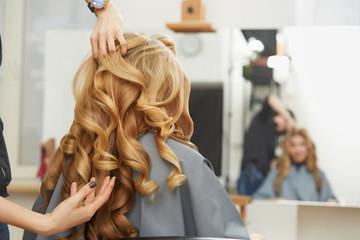 Blond kręcone włosy. Fryzjer robi fryzurę dla młodej kobiety i