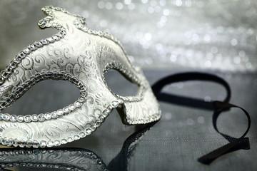 Vintage carnival mask in front of glittering background