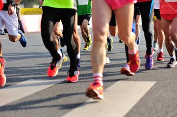 marathon athletes legs running on city road