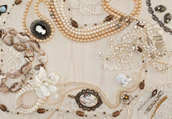 Beautiful female jewelry and trinkets on a light wooden backgrou