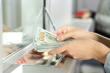 Female hand with money in cash department window. Currency