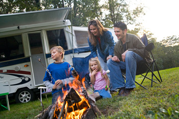 Camping: Family Having Fun With Marshmallows By The Fire