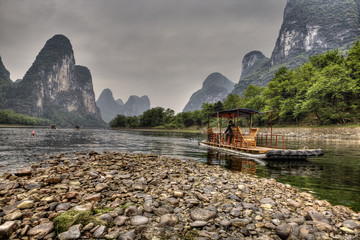Bamboo raft on Lijiang River, amid karst hills, Guangxi, China.