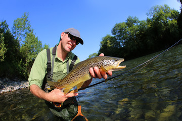 Closeup of fly-fisherman holding brown truit in river