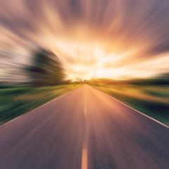 archiwalne zdjęcie kraju drogi asfaltowej w ruchu rozmycie o zachodzie słońca.