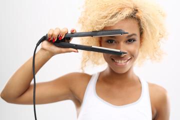 Prostownica do włosów. Młoda dziewczyna prostuje włosy za pomocą prostownicy