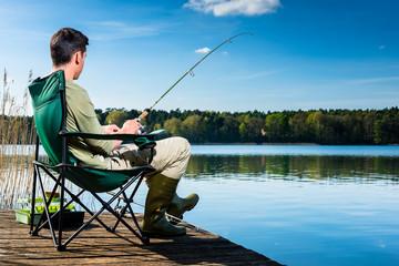 Mann beim Angeln am See sitzt auf Steg