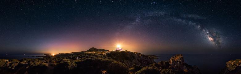 Prostoliniowy widok 360 ° gwiaździstej nocy z łukiem Drogi Mlecznej i latarnią morską Capo Spartivento