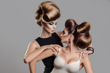 Studio photo of two beauty women with creative hairstyle looking