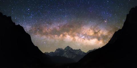 """Miska Niebios. Jasna i żywa galaktyka Drogi Mlecznej nad zaśnieżonymi górami. Piękne gwiaździste nocne niebo wydaje się znajdować w """"misce"""" między sylwetkowymi wzgórzami."""