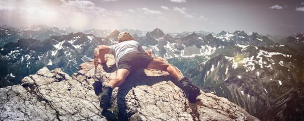 Man Scrambling Over Rocks on Mountain Ledge