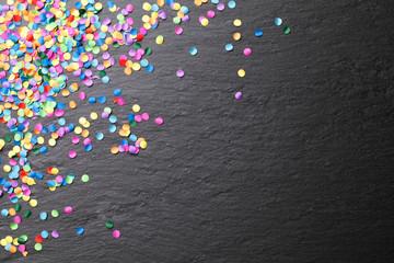 Konfetti bunt auf schwarzer Kreide Tafel Hintergrund