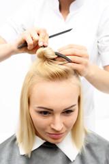 Włosy półdługie, kobieta u fryzjera. Kobieta na fotelu fryzjerskim podczas zabiegu stylizacji włosów
