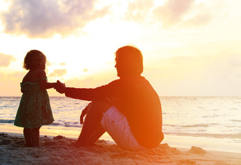 Father and little daughter holding hands at sunset