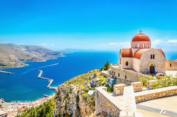 Daleki kościół z czerwonym zadaszeniem na falezie, Grecja