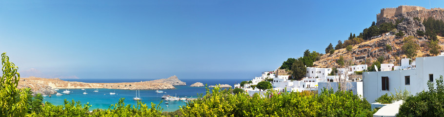 Greece. Rhodes. The picturesque sea bay and town of Lindos with its medieval castle and the Acropolis