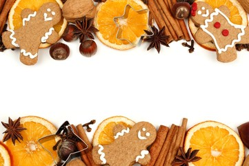 Double border of Christmas gingerbread men and holiday spices over a white background
