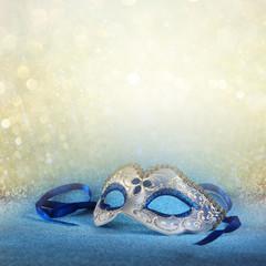 blue female carnival mask and glitter background