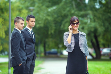 Attractive new female coworker passing by two young businessmen on the street
