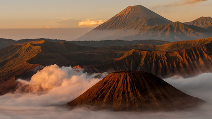 Smoking Volcano Bromo with fog and mist at sunrise in Indonesia