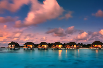 Water bungalows with beautiful twilight sky and sea in Maldives. Long Exposure.