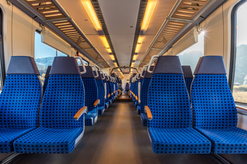 Image with the interior of a german border train. A modern train with comfortable and colorful chairs.