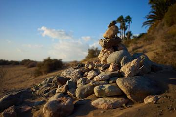 Sterty kamieni na pustyni / Piaszczyste i kamieniste wydmy ze stylowymi formami na szerokiej pustyni pod niebieskim niebem