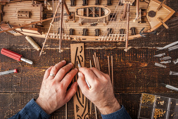 Man collects the vehicle model on the wooden table