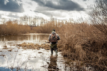 myśliwy skradający się na bagnach w okresie polowań