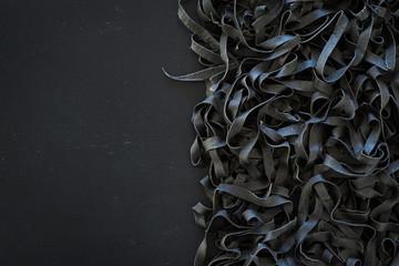 Domowe niegotowane czarny tagliatelle atramentu kałamarnicy na czarnym tle