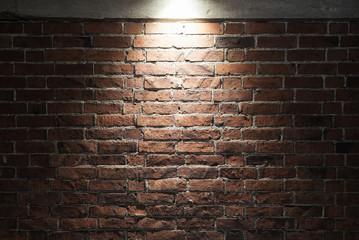 Grungy dark red brick wall with spotlight, texture