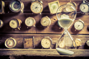 Vintage hourglass on the background of clocks