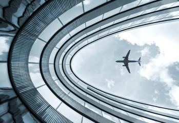 Niski widok niebieski pokolorowane zdjęcie nowoczesnej architektury budynku z lądowaniem samolotu w tle