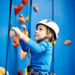 Little boy is climbing in sport park on blue wall