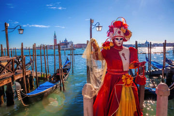 Carnival masks against gondolas in Venice, Italy