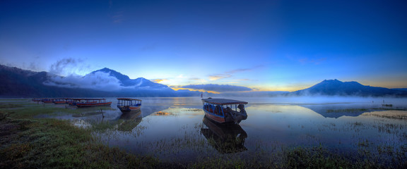 Boats wait for passengers. View of boats leaning on the lake in the early of the dawn in kintamani lake bali